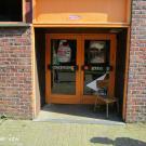 De toegang tot de lokalen is drempelloos. Op de deur (handgrepen) staat de naam van de jeugdvereniging duidelijk vermeld. (Chirojongens WIJ, Koersel)