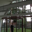 De toegang is drempelloos. Om veiligheidsredenen worden glazen deuren voorzien van een contrastmarkering om ze beter zichtbaar te maken. (Chiro St-Jan, Kachtem)