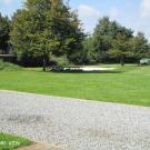 Er is een groot grasveld aanwezig als speelruimte. Kiezels worden best vermeden als ondergrond voor paden. Optimaal worden paden vlak en rolstoelvast uitgevoerd. (Jeugdhuis Bascule, Eversel)